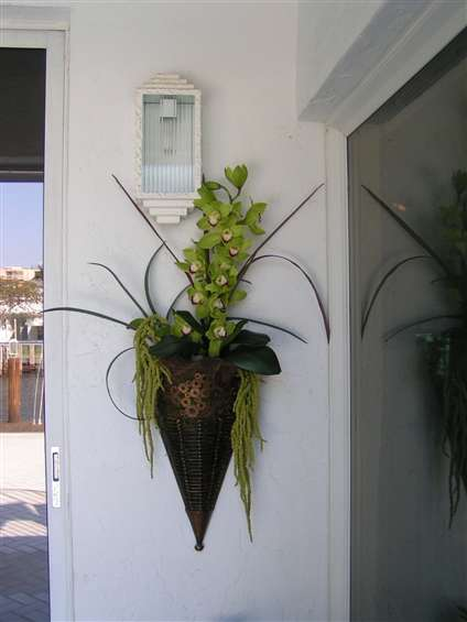 Green Cymbidium orchid arrangement in metal container.