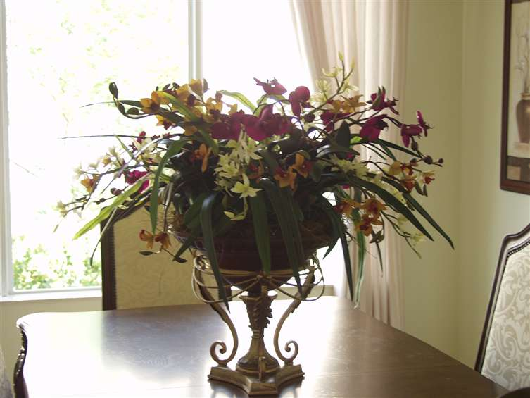 Mixed orchids in urn. By Paolo Calvenzani